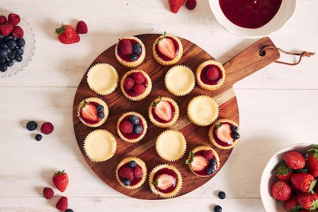 Petits gâteaux au fromage avec gelée de fruits et fruits sur une plaque en bois