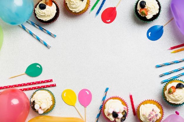 Petits gâteaux avec des ballons à air et des bougies sur table