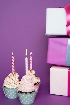 Petits gâteaux avec une bougie allumée à côté de cadeaux