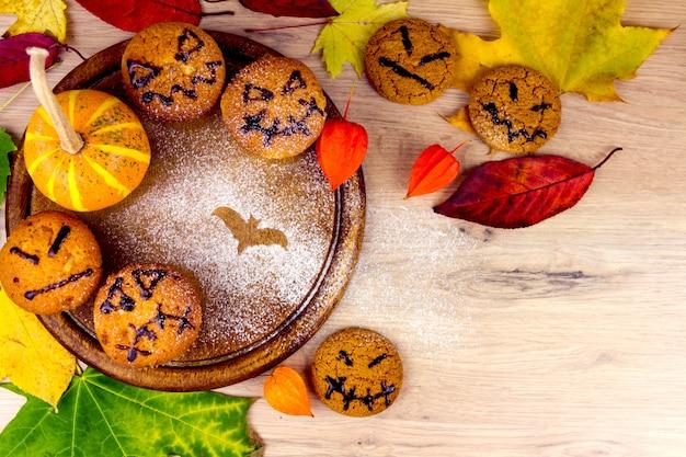 Petits gâteaux, citrouille, feuilles et silhouette de chauve-souris sur des plats en bois