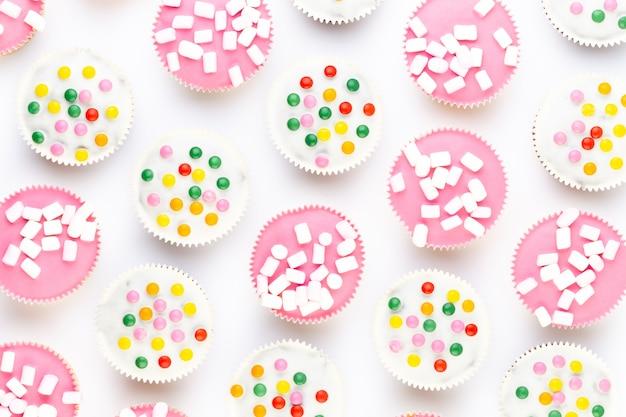 Petits gâteaux colorés sur fond blanc.