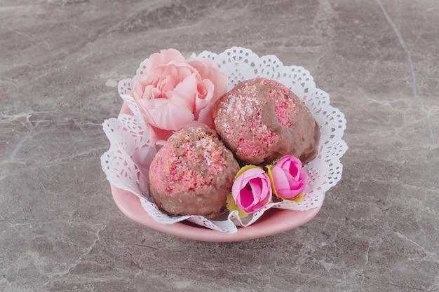 Petits gâteaux et corolles de fleurs dans un bol recouvert de napperon sur marbre