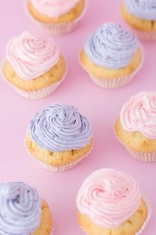 Petits gâteaux avec crème au beurre rose et violet se tenant debout sur la vue de dessus de fond rose pastel.