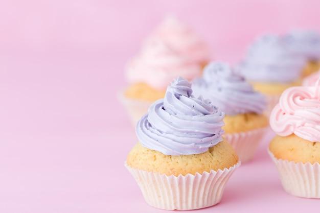 Petits gâteaux avec crème au beurre rose et violet se tenant sur fond rose pastel.