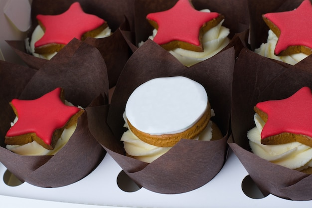 Petits gâteaux à la crème et étoiles rouges sur fond blanc.