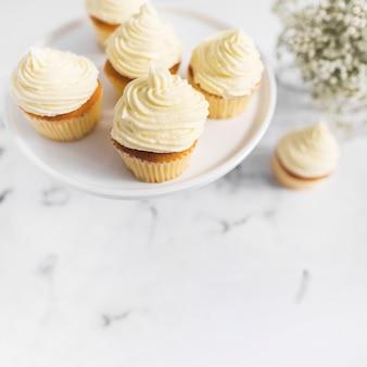 Petits gâteaux à la crème fouettée sur un support de gâteau