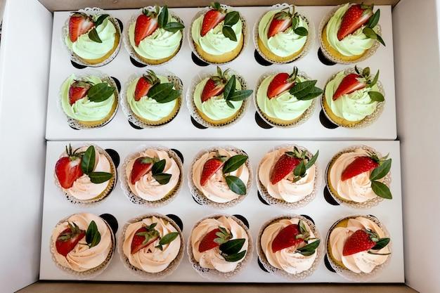 Petits gâteaux à la crème avec des fraises sur table en bois.