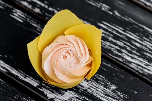 Petits gâteaux à la crème rose fait maison avec des fraises sur la table en bois.
