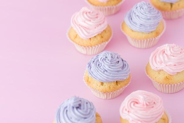Petits gâteaux avec crème violette et rose se tenant debout sur la vue de dessus de fond rose pastel.