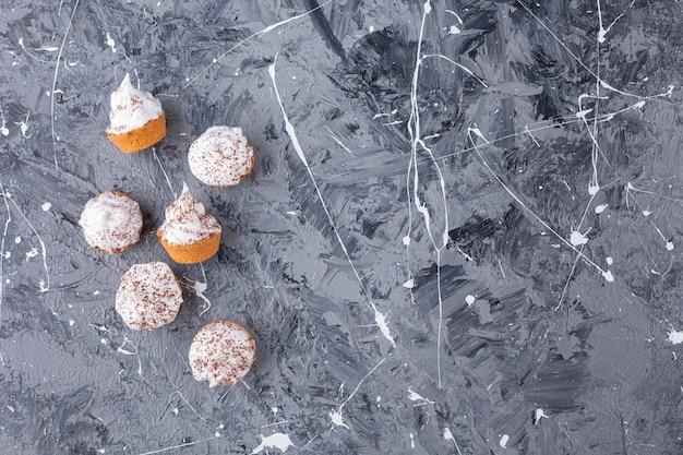 Petits gâteaux crémeux sucrés éparpillés sur du marbre.