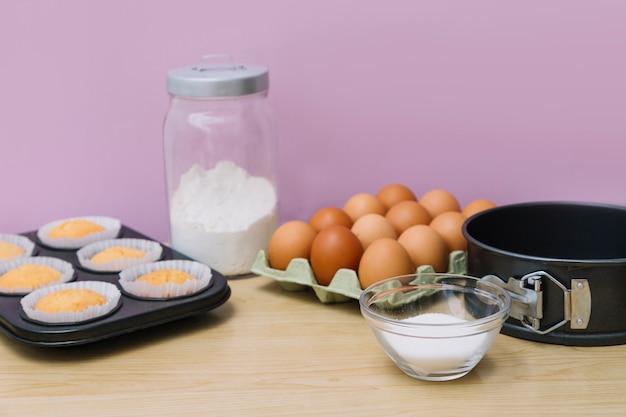 Petits gâteaux cuits au four dans une plaque à pâtisserie avec des ingrédients sur un bureau en bois sur fond rose