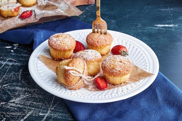 Petits gâteaux dans une assiette blanche.