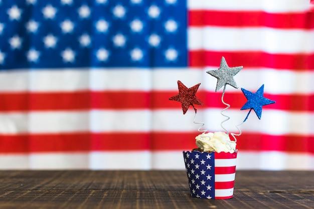 Petits gâteaux décoratifs avec du rouge; étoiles argentées et bleues sur un bureau en bois contre des drapeaux américains pour le 4 juillet