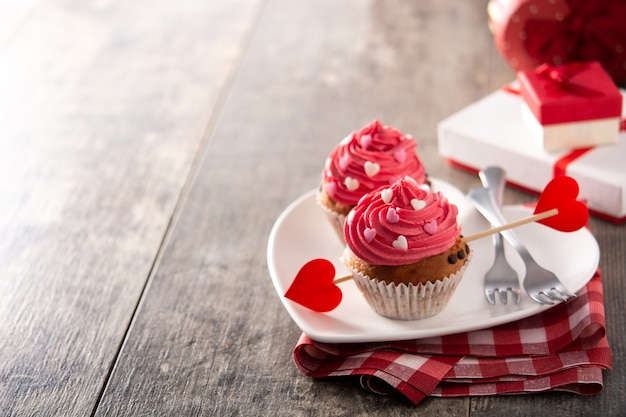 Petits gâteaux décorés de coeurs en sucre pour la saint-valentin sur table en bois