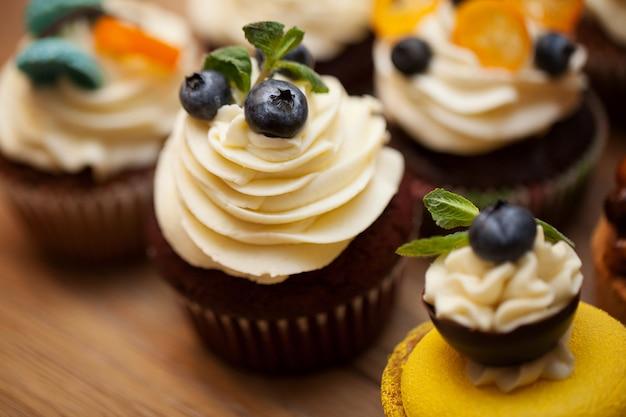 Petits gâteaux délicieux avec des baies sur une table en bois se bouchent