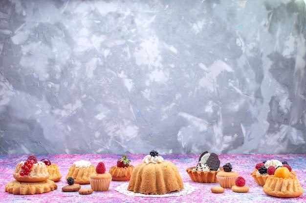 Petits gâteaux délicieux avec de la crème avec des baies sur un gâteau lumineux, biscuit berry sweet bake