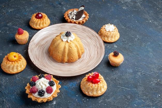 Petits gâteaux délicieux différents formés sur un gâteau biscuit foncé aux fruits sucrés