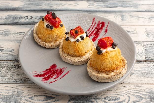 Petits gâteaux délicieux avec des fruits à la crème et de la marmelade sur le dessus à l'intérieur de la plaque pourpre sur fond gris