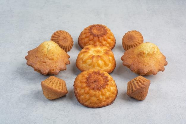 Petits gâteaux délicieux sucrés sur table blanche.