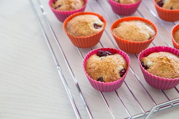 Petits gâteaux faits maison avec des cerises, des muffins sur une grille sur une table blanche