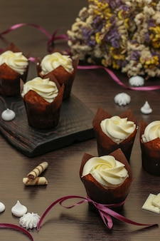 Petits gâteaux faits maison avec de la crème sur fond sombre, concept pour la saint-valentin, anniversaire et fête des pères, gros plan