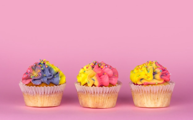 Petits gâteaux faits maison avec de la crème multicolore sur un espace de copie de fond rose. crème jaune et rose.