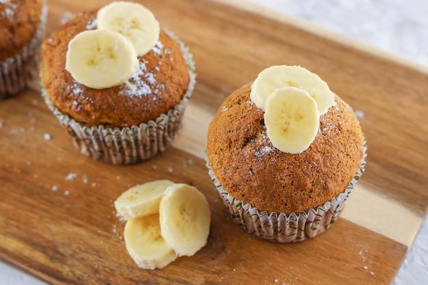 Petits gâteaux faits maison avec ingrédient banane sur planche de bois, recette de muffins faciles, fond de boulangerie