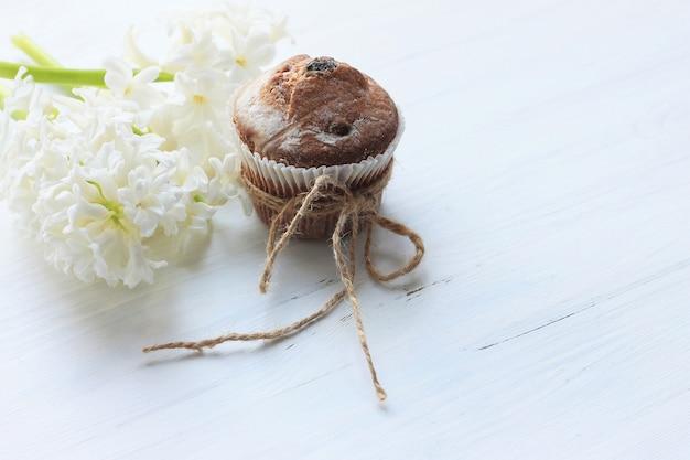 Petits gâteaux et fleurs sur un fond en bois blanc