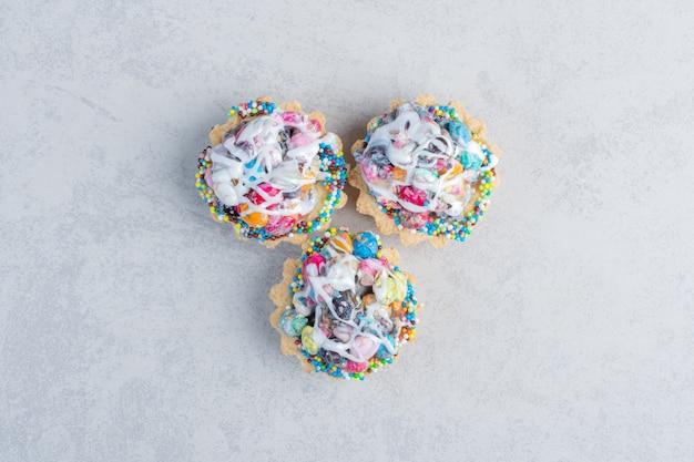 Petits gâteaux avec garnitures de bonbons regroupés sur une surface en marbre