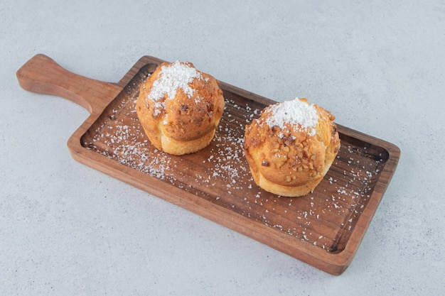 Petits gâteaux avec garnitures en poudre de vanille sur un plateau sur fond de marbre.