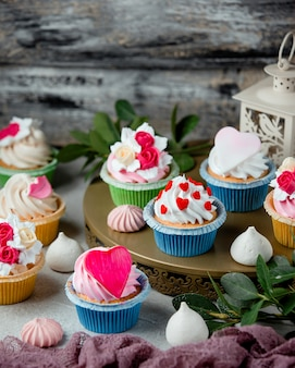 Petits gâteaux mignons décorés de coeurs de crème fouettée et de fleurs