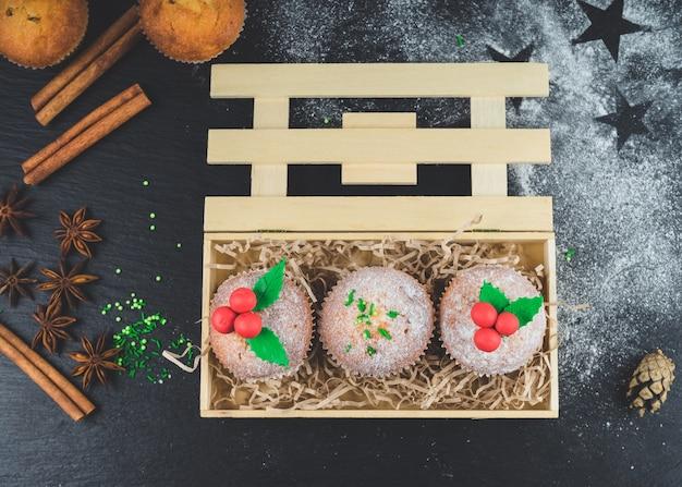 Petits gâteaux de noël décorés de gui dans une boîte en bois