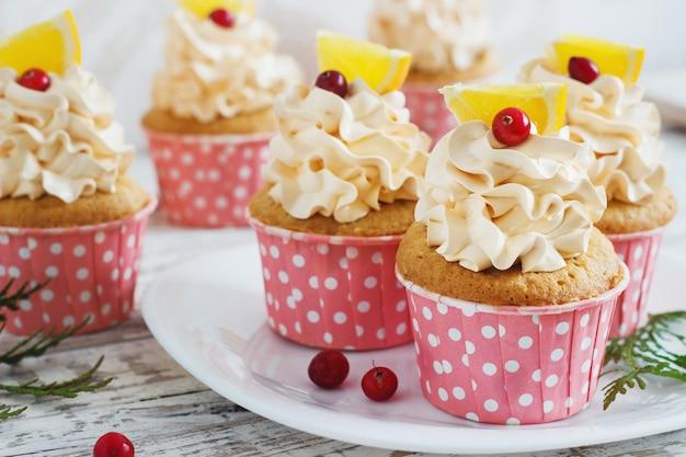 Petits gâteaux de noël avec garniture à la crème fouettée et canneberges, orange. dessert festif alimentaire.