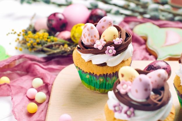 Petits gâteaux de pâques décorés avec des œufs de bonbons au nid sur la table du dîner de pâques