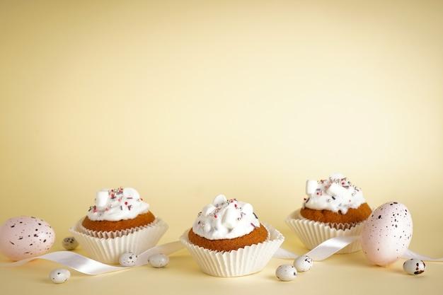 Petits gâteaux de pâques et oeufs de pâques sur fond jaune avec espace copie