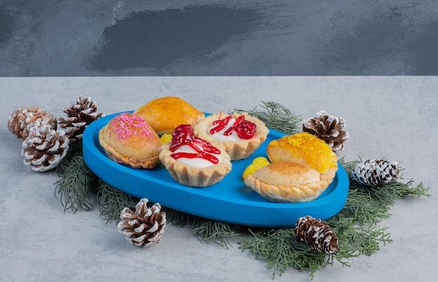 Petits gâteaux, petits pains et bonbons à la gelée sur un plateau bleu décoré de feuilles de pin et de cônes sur une surface en marbre