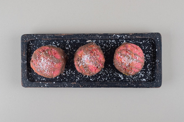Petits gâteaux sur un plateau noir sur fond de marbre.