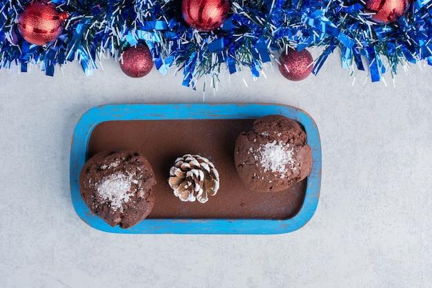 Petits gâteaux et une pomme de pin sur un plateau à côté d'une guirlande et des boules sur une surface en marbre