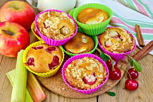 Petits gâteaux à la rhubarbe, cerises, pommes dans des moules en silicone, lait dans une cruche, une serviette sur un fond de planches de bois