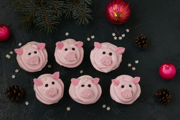Petits gâteaux roses faits maison décorés avec de la crème protéinée et des piggies drôles en forme de guimauve