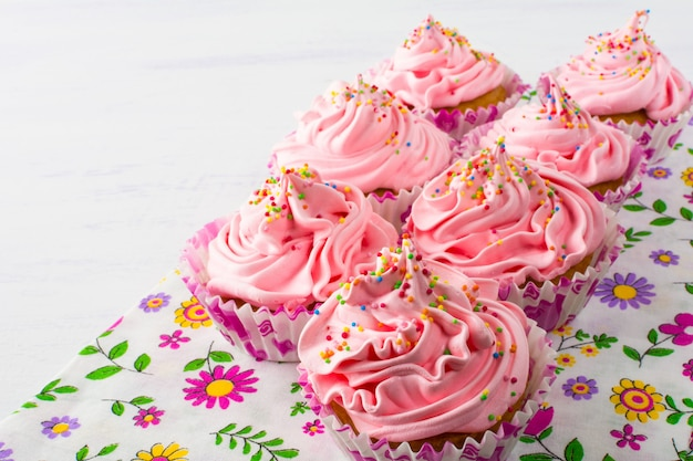 Petits gâteaux roses sur une serviette florale