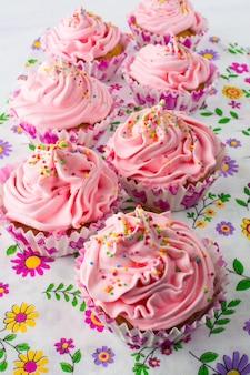 Petits gâteaux roses sur une serviette à motif floral