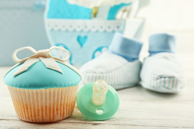 Petits gâteaux savoureux avec arc et chaussures de bébé, landau décoratif et album photo sur fond de couleur