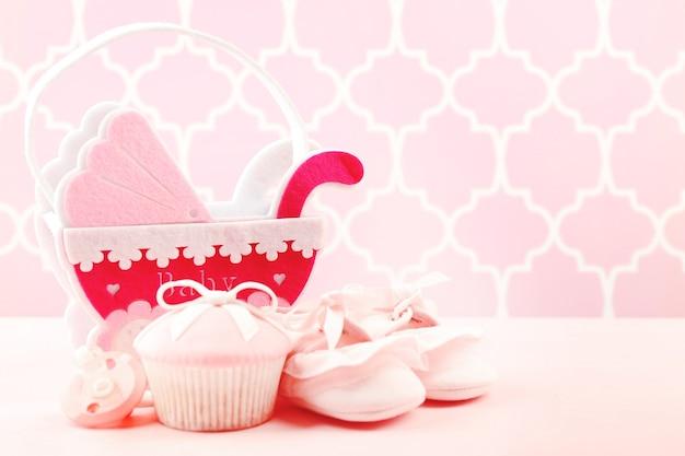 Petits gâteaux savoureux avec arc et chaussures de bébé, landau décoratif sur fond de couleur