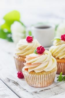 Petits gâteaux à la vanille à la crème et framboises sur une table en bois blanche