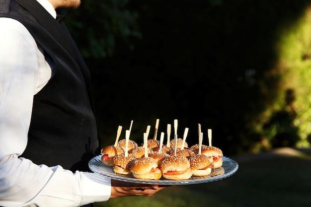 Petits hamburgers servis sur une assiette tenue par le serveur
