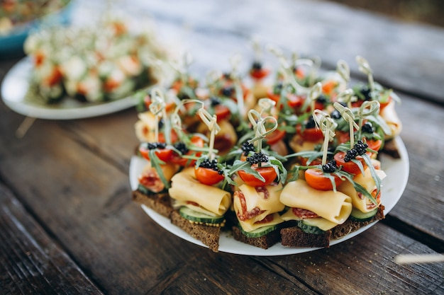 Petits hamburgers avec de la viande, du fromage de salade et des tomates sur une plaque en bois pendant l'été barbecue party en plein air.