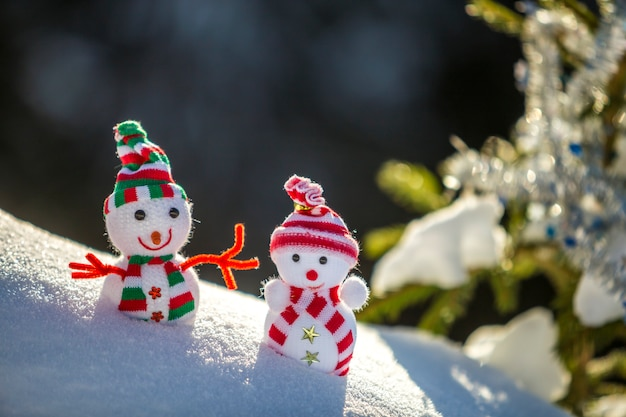 Petits jouets drôles bébé bonhomme de neige dans des chapeaux et des écharpes en tricot dans la neige profonde à l'extérieur près d'une branche de pin.