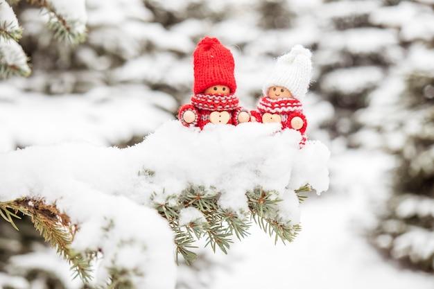 Petits jouets mignons de noël sur une branche de sapin couverte de neige