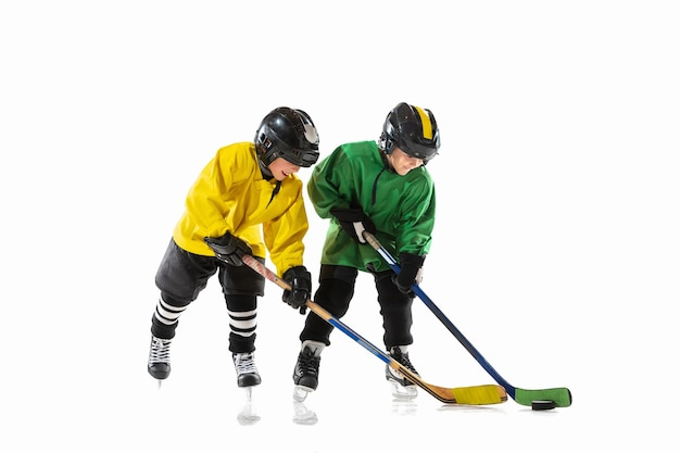 Petits joueurs de hockey avec les bâtons sur un court de glace et fond blanc.